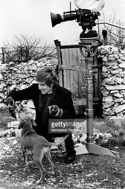 Italian actor Enzo Cerusico on the set of the movie Anche se volessi lavorare che faccio he is crouched and feeds a dog beside them there is a movie...
