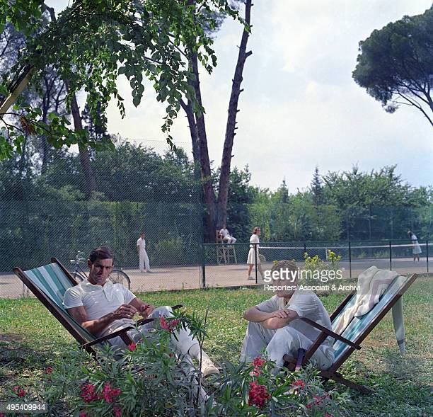 Italian actor Fabio Testi and Austrian actor Helmut Berger sitting on two beach chairs in a scene from the film The Garden of the FinziContinis Italy...