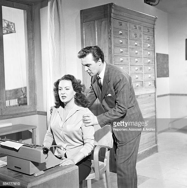 Italian actor Franco Fabrizi touching Greekborn Italian actress Yvonne Sanson's shoulders while she's sitting at the desk in the film Torna 1953