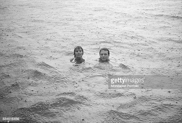 Italian actor Franco Interlenghi and his wife Italian actress Antonella Lualdi bathing under the rain during the XVIII Venice International Film...