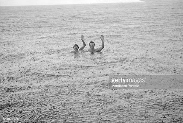 Italian actor Franco Interlenghi and his wife Italian actress Antonella Lualdi waving hands in the sea under the rain during the XVIII Venice...