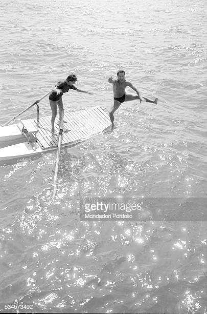 Italian actor Franco Interlenghi and his wife Italian actress Antonella Lualdi diving from a boat during the XVIII Venice International Film Festival...