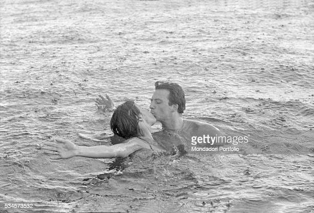 Italian actor Franco Interlenghi and his wife Italian actress Antonella Lualdi kissing in the sea under the rain during the XVIII Venice...