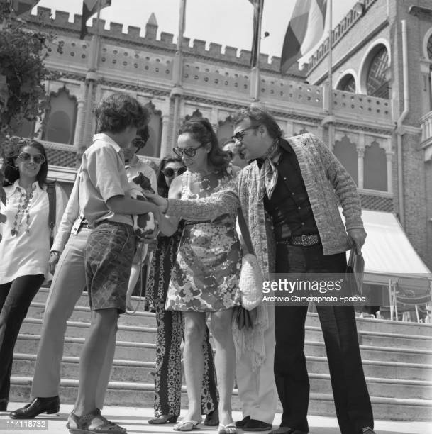 Italian actor Giorgio Albertazzi with wife Anna Proclemer standing on the Excelsior Hotel stairs in Lido Venice and caressing a pet They're both...