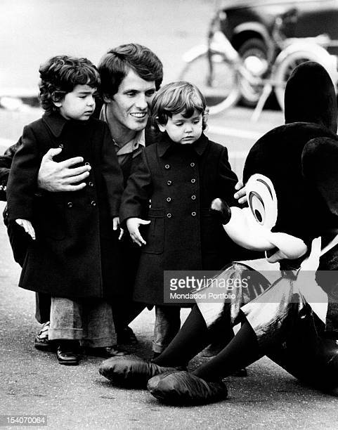Italian actor Giuliano Gemma and his daughters Vera and Giuliana having fun with Mickey Mouse of the crew Disney on Parade Rome 1972