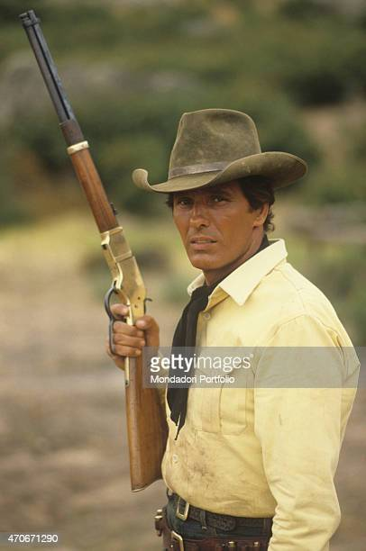 """Italian actor Giuliano Gemma holding a rifle on the set of the film Tex and the Lord of the Deep. Italy, 1985 """
