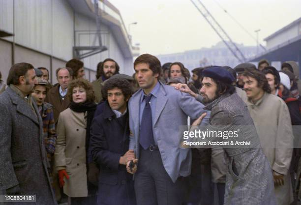 "Italian actor Giuliano Gemma on the set of the film ""Somewhere Beyond Love"". He's standing on a building site and being stopped by other people. 1974"