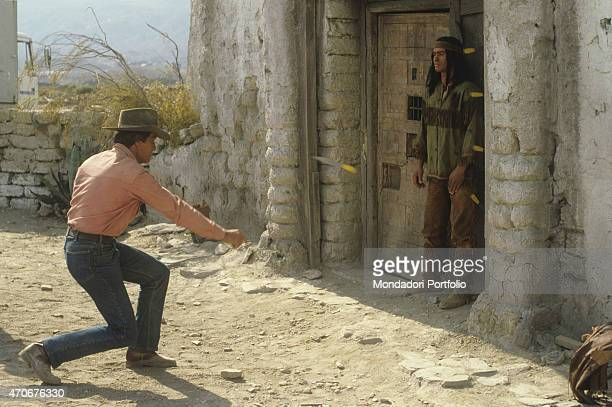 """Italian actor Giuliano Gemma throwing knives at Italian actor Carlo Mucari on the set of the film Tex and the Lord of the Deep. Italy, 1985 """