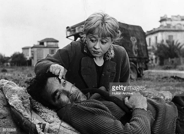 Italian actor Giulietta Masina raising Mexicanborn actor Anthony Quinn's eyebrow with her finger as Quinn iies on the ground in a still from director...