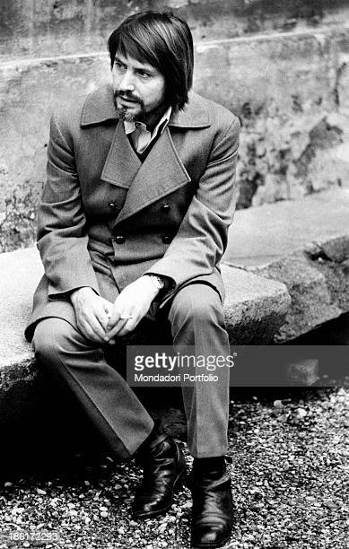 Italian actor Giulio Brogi is shot outdoors while he is seated on a stone and gazes into the distance with a serious look Rome 1971