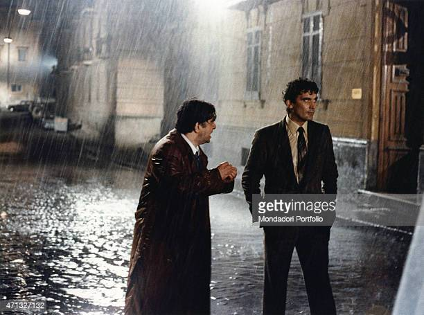 Italian actor Lello Arena talking to Italian actor and director Massimo Troisi under the rain in the film Scusate il ritardo 1983