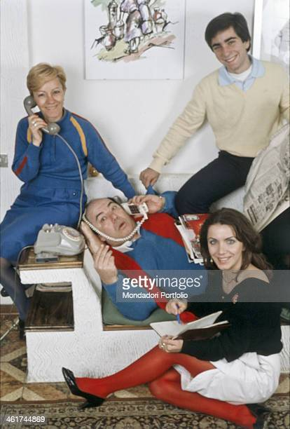 Italian actor Lino Banfi lying on a sofa pretending to speak on the telephone with his wife Lucia Agresta and their children Walter Banfi and Rosanna...