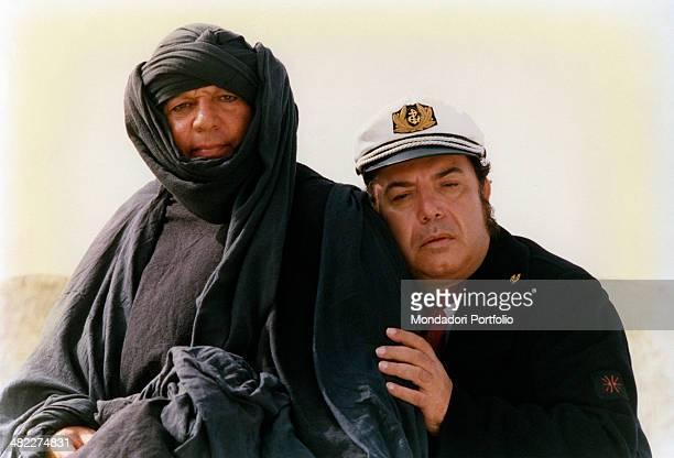 Italian actor Lino Banfi resting against Italian actor Paolo Villaggio dressed as a Tuareg in the film Com'è dura l'avventura 1987