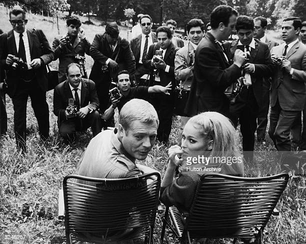 Italian actor Marcello Mastroianni and Swiss actor Ursula Andress sit outdoors while photographers take their picture on the set of director Elio...