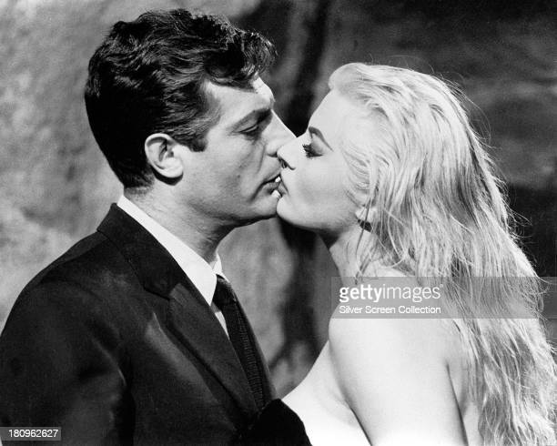 Italian actor Marcello Mastroianni as Marcello Rubini and SwedishAmerican actress Anita Ekberg as Sylvia kissing in 'La Dolce Vita' directed by...