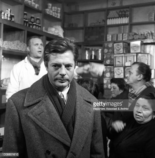 """Italian actor Marcello Mastroianni in a scene from the film """"Family Diary"""" directed by Italian director Valerio Zurlini. He's standing in a grocery..."""