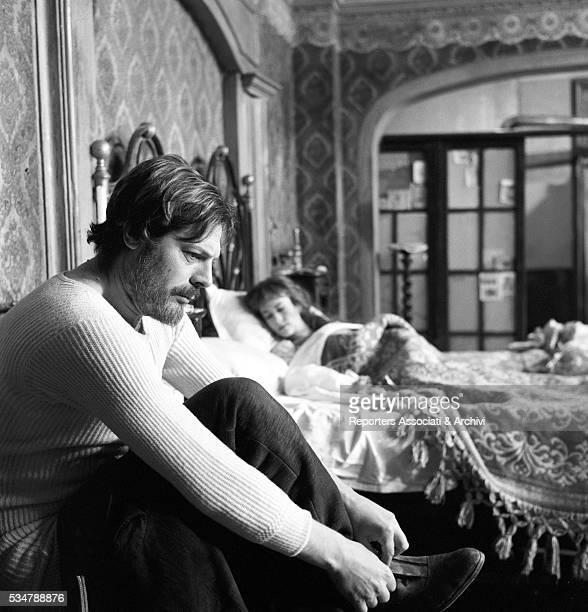 Italian actor Marcello Mastroianni lacing his shoes in the film The Organizer 1963