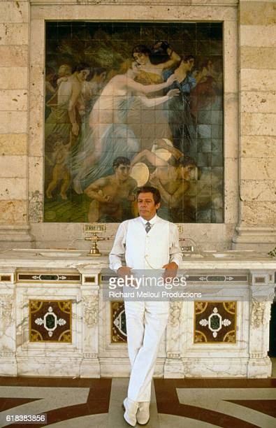 Italian actor Marcello Mastroianni leans on a pedestal in front of a painting on the set of the film Oci Ciornie. The Italian film, called Dark Eyes...