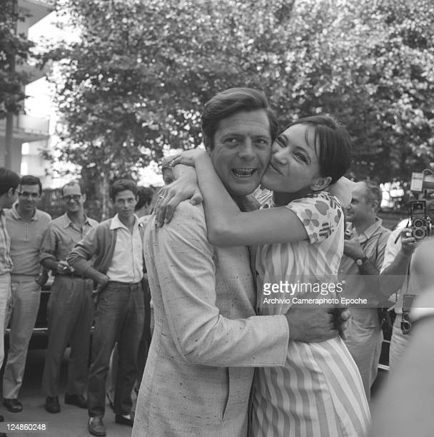 Italian actor Marcello Mastroianni portrayed with the swedish actress Anna Karina surrounded by photographers while presenting the movie 'L'Etranger'...