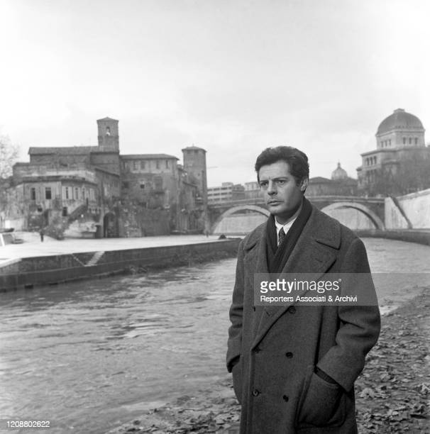 """Italian actor Marcello Mastroianni standing by the Tiber river with the Tiber Island in Rome behind him in the film """"Family Diary"""" directed by..."""