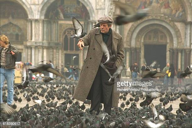 Italian actor Marcello Mastroianni surrounded by pigeons in Piazza San Marco in Venice Italy