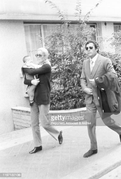 Italian actor Marcello Mastroianni walking with his partner and French actress Catherine Deneuve by his side and their daughter Chiara in her arms....
