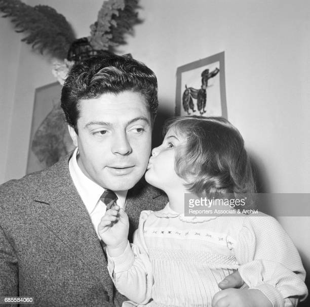 Italian actor Marcello Mastroianni with his daughter Barbara kissing him on his cheek during a photoshooting at home Italy 1955