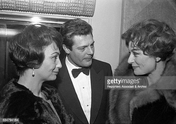 Italian actor Marcello Mastroianni with his wife Flora Carabella and French actress Anouk Aimée at the premiere of the film La Dolce Vita played at...
