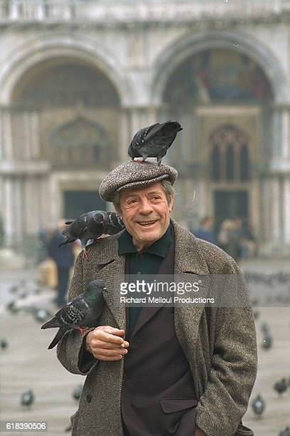 Italian actor Marcello Mastroianni with pigeons in Piazza San Marco in Venice Italy