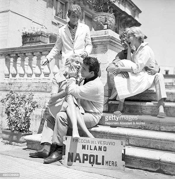 Italian actor Maurizio Arena Italian actress Alessandra Panaro and Italian actor Renato Speziali sitting on some steps in a scene from the film...