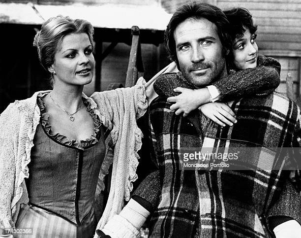 Italian actor Maurizio Merli carrying Matteo Zoffoli piggyback in the film White Fang to the Rescue German actress Gisela Hahn watches at them Rome...