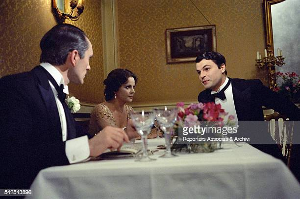 Italian actor Michele Placido British actor Terence Stamp and Italian actress Laura Antonelli sitting at a table in The Divine Nymph 1975