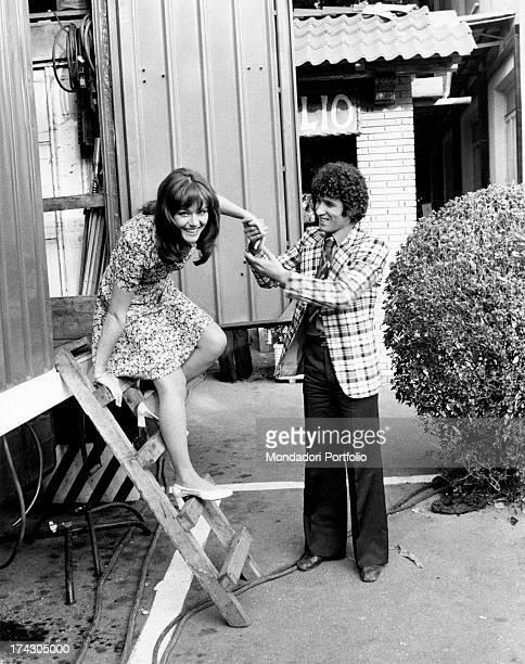 Italian actor Ninetto Davoli helping Italian actress Agostina Belli to go down a ladder Rome 1970s