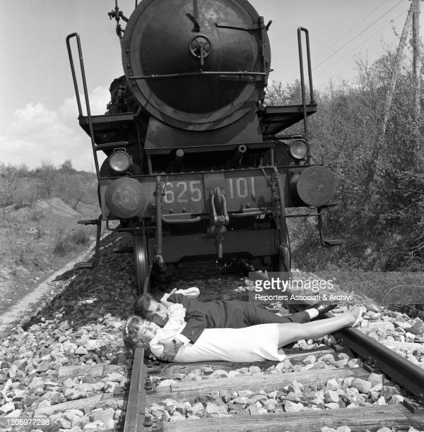 Italian actor Nino Manfredi and American actress Pamela Tiffin hugging each other and lying on the rails in the film Kill Me with Kisses. 1968