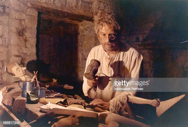 Italian actor Nino Manfredi as Geppetto making Pinocchio on a woodworker table in the TV miniseries The Adventures of Pinocchio 1972