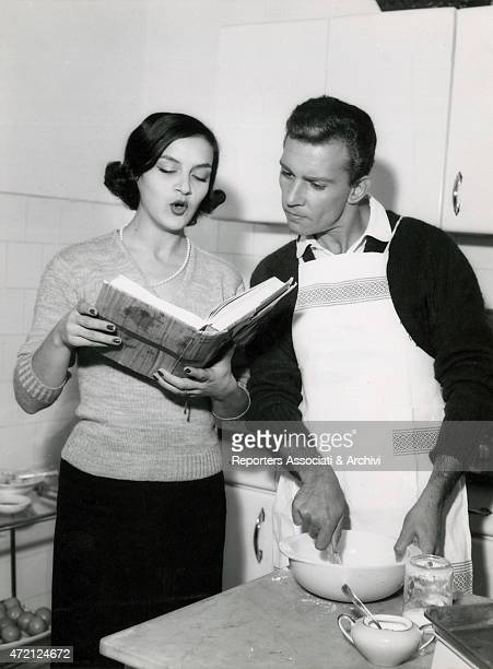 'Italian actor Paolo Ferrari and his wife Italian actress Marina Bonfigli reading and cooking a recipe 1950s '