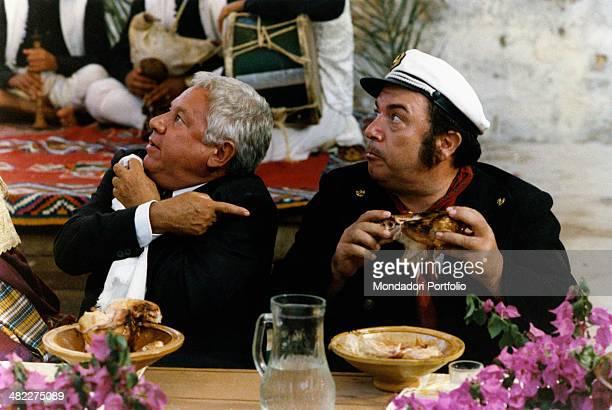 Italian actor Paolo Villaggio pointing at Italian actor Lino Banfi holding a chicken in the film Com'è dura l'avventura 1987