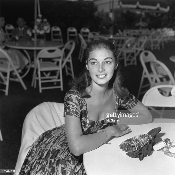 Italian actor Pier Angeli sits at a patio table wearing a floral print dress at a Louella Parsons' party Los Angeles California mid 1950s