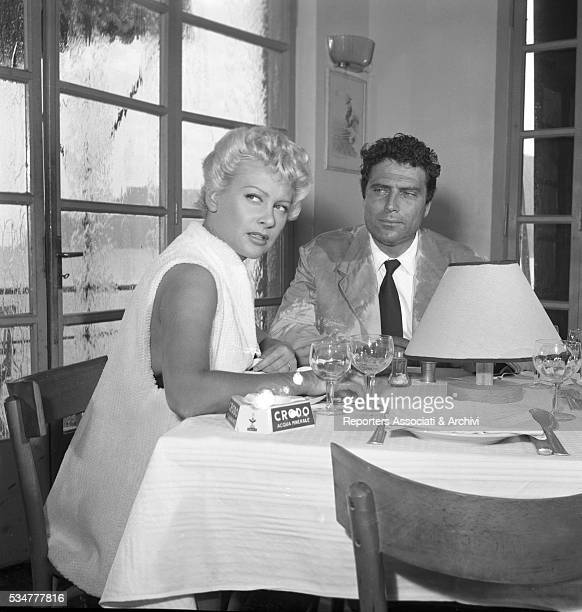 Italian actor Raf Vallone posing with French actress Martine Carol on the set of The Beach Italy 1953
