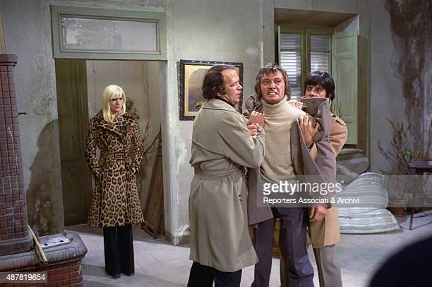 Italian actor Renato Salvatori and Italian actor director and scriptwriter Giancarlo Giannini trying to hold Italian actor and director Adalberto...