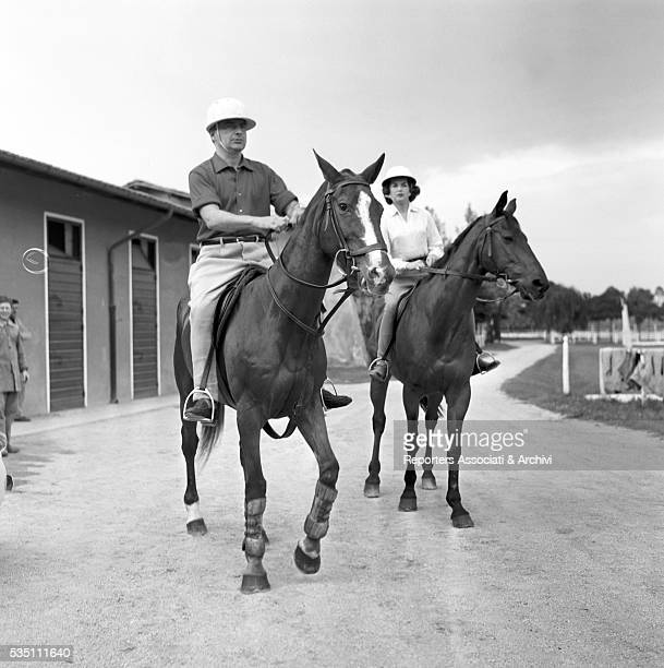 Italian actor Rossano Brazzi and British actress Dawn Addams riding two horses before a match of polo Rome 1957