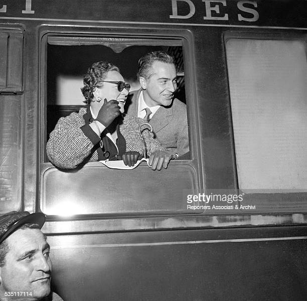 Italian actor Rossano Brazzi and his wife Lidia Bertolini appearing at their train window while coming back from Paris at Termini railway station...