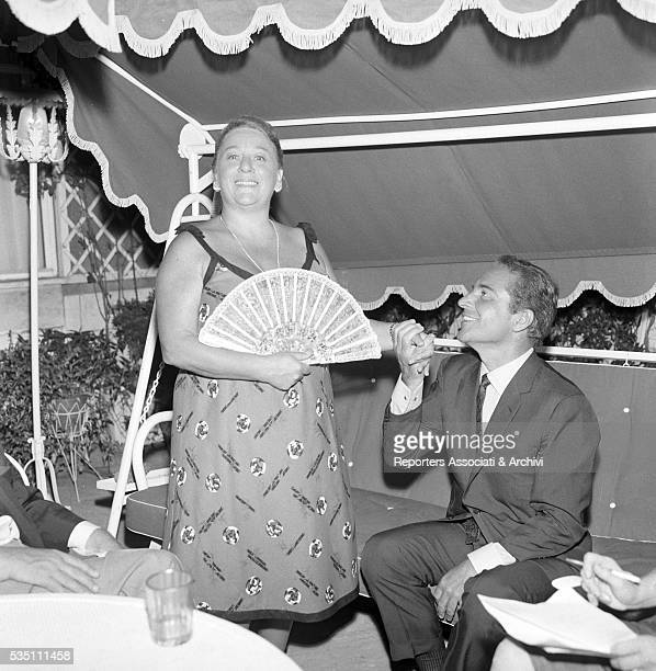 Italian actor Rossano Brazzi and his wife Lidia Bertolini hand in hand during an evening on their terrace 21st August 1965
