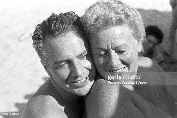 Italian actor Rossano Brazzi and his wife Lidia Bertolini smiling in a day at the beach 15th July 1958