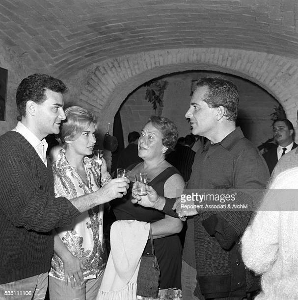 Italian actor Rossano Brazzi and his wife Lidia Bertolini toasting at the party held in the house of Italianborn Swiss singer Teddy Reno and his wife...