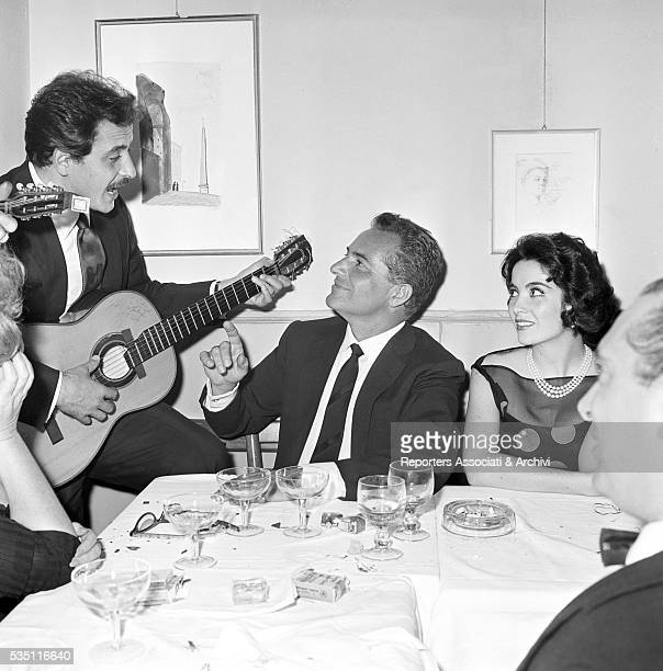 Italian actor Rossano Brazzi - beside Argentinian actress Linda Cristal - singing accompanied by Italian singer-songwriter Domenico Modugno at the...