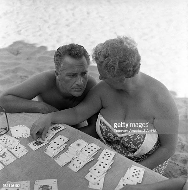 Italian actor Rossano Brazzi beside his wife Lidia Bertolini playing cards at the beach Fregene August 1959