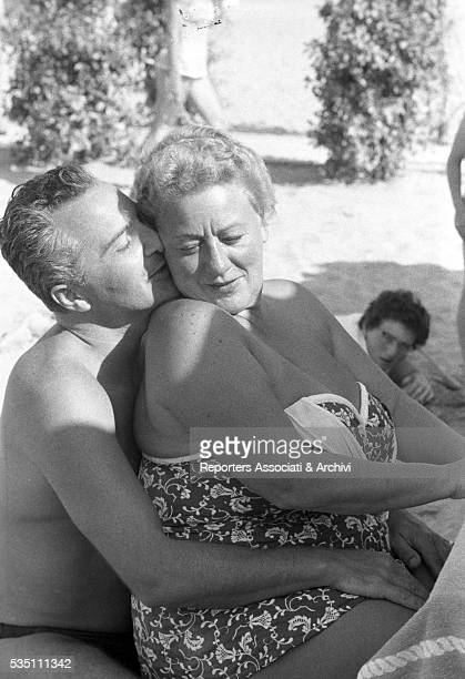 Italian actor Rossano Brazzi hugging his wife Lidia Bertolini in a day at the beach 15th July 1958