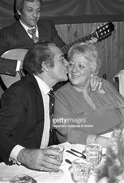 Italian actor Rossano Brazzi kissing his wife Lidia Bertolini during a dinner after a cinema premiere 1977