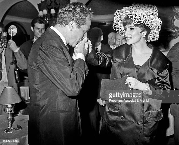 Italian actor Rossano Brazzi kissing Italian actress Gina Lollobrigida's hand at the party in a villa in Grottaferrata Roma Castles with many guests...